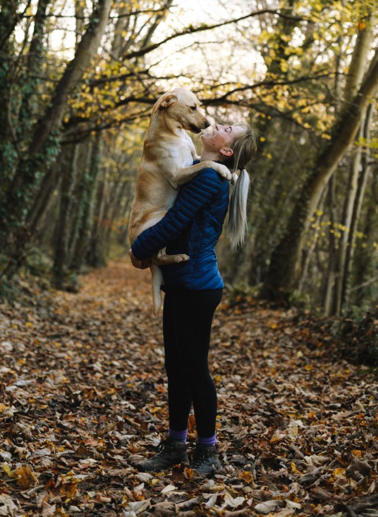 Young woman holding her dog in her arms for a cuddle